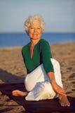 Ältere Frau, die Yoga auf dem Strand genießt Stockfotografie