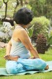 Ältere Frau, die Yoga am Park tut Stockfoto