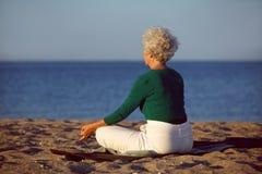 Ältere Frau, die Yogameditation auf Strand tut Stockfotografie