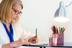 Ältere Frau, die Zeit mit Malbuch verbringt Lizenzfreie Stockfotografie