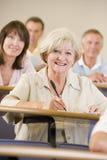 Ältere Frau, die zu einem Hochschulvortrag hört Stockbild