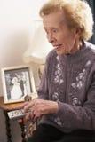 Ältere Frau, die zu Hause Fernsieht Stockfotos