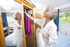 Ältere Frau, die zu Hause Kleid vom Wandschrank vorwählt lizenzfreies stockbild