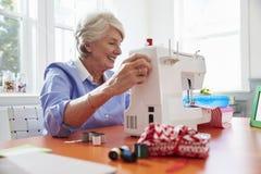 Ältere Frau, die zu Hause Kleidung unter Verwendung der Nähmaschine herstellt lizenzfreie stockbilder