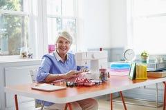Ältere Frau, die zu Hause Kleidung unter Verwendung der Nähmaschine herstellt stockfotos