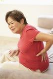 Ältere Frau, die zu Hause unter den rückseitigen Schmerz leidet Stockbilder