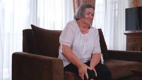 Ältere Frau, die zu Hause unter den Schmerz im Knie leidet stock footage