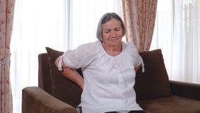 Ältere Frau, die zu Hause unter Rückenschmerzen leidet stock video