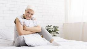 Ältere Frau, die zu Hause weißes Kissen umarmt stockfotografie