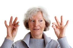 Ältere Frau, die zwei Pillen vergleicht Stockfotografie