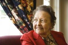 Ältere Frau durch Fenster. lizenzfreie stockfotografie
