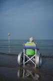 Ältere Frau in einem Rollstuhl im Meer lizenzfreie stockbilder