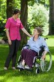 Ältere Frau in einem Rollstuhl mit einer Krankenschwester Stockbilder