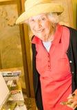 Ältere Frau, einen Sonnenhut tragend und malen an ihrem Gestell lizenzfreie stockfotografie