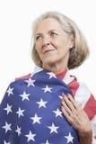 Ältere Frau eingewickelt in der amerikanischen Flagge gegen weißen Hintergrund Lizenzfreies Stockfoto