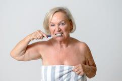 Ältere Frau eingewickelt im Tuch, das ihre Zähne putzt Stockfotos