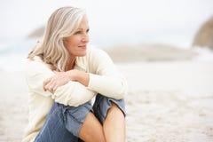 Ältere Frau am Feiertag, der auf Strand sitzt Lizenzfreies Stockbild