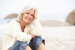 Ältere Frau am Feiertag, der auf Winter-Strand sitzt Stockfotografie