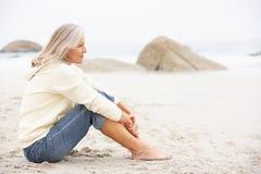 Ältere Frau am Feiertag, der auf Winter-Strand sitzt Lizenzfreies Stockbild
