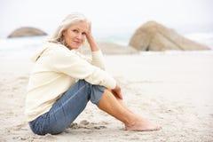 Ältere Frau am Feiertag, der auf Winter-Strand sitzt Stockfoto