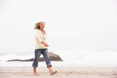 Ältere Frau am Feiertag, der entlang Strand läuft Stockfotos