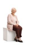Ältere Frau gesetzt auf einem Würfel lizenzfreie stockbilder