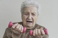 Ältere Frau hebt schwierig die Dummköpfe an lizenzfreie stockfotos