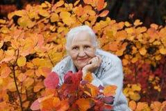 Ältere Frau am Herbsthintergrund Stockfotografie