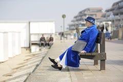 Ältere Frau im blauen Mantel u. im Hut auf einer Bank Stockfotos