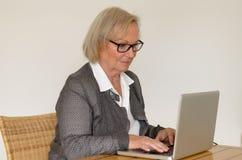 Ältere Frau im Geschäftsblick vor einem silbernen Laptop Lizenzfreie Stockbilder