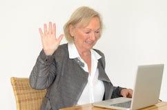 Ältere Frau im Geschäftsblick vor einem silbernen Laptop Stockfotos