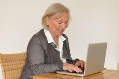 Ältere Frau im Geschäftsblick vor einem silbernen Laptop Stockfoto