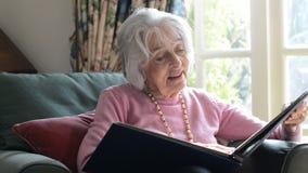Ältere Frau im Lehnsessel zu Hause, der Foto-Album betrachtet stock footage