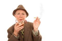 Ältere Frau im Luftwiderstand mit Zigarette und alkoholischem Getränk Lizenzfreie Stockfotografie