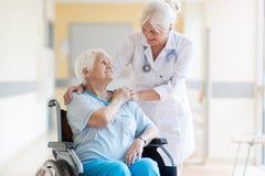 Ältere Frau im Rollstuhl mit Ärztin im Krankenhaus lizenzfreie stockfotos