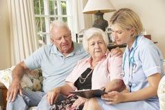 Ältere Frau im Ruhestand, die Gesundheits-Check mit Krankenschwester At Home hat Stockbild
