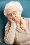 Ältere Frau im Stuhl zu Hause Lizenzfreie Stockbilder