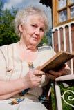 Ältere Frau liest ein Buch Lizenzfreie Stockfotos