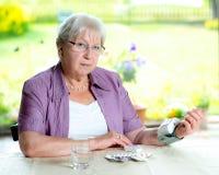 Ältere Frau misst Blutdruck Stockbilder