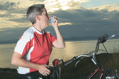 Ältere Frau mit Asthmainhalationsapparat auf Fahrrad an Lizenzfreies Stockbild