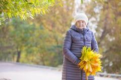 Ältere Frau mit Bündel Herbstlaub lizenzfreie stockfotos