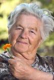 Ältere Frau mit Blume lizenzfreie stockfotos