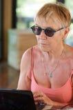 Ältere Frau mit Computer Stockbild
