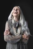 Ältere Frau mit dem Arme gefalteten Lachen Lizenzfreies Stockfoto