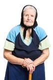 Ältere Frau mit dem Spazierstock, der auf Weiß steht Lizenzfreie Stockbilder