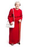 Ältere Frau mit dem Spazierstock, der auf Weiß steht Stockbild