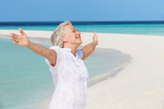 Ältere Frau mit den Armen ausgestreckt auf schönem Strand Stockfotos