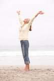 Ältere Frau mit den Armen streckte auf Strand aus Stockfotografie