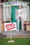 Ältere Frau mit den gekreuzten Armen, die auf Portal des neuen Hauses stehen und Verkaufszeichen auf grünem Gras Lizenzfreie Stockfotos