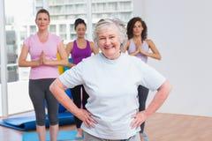 Ältere Frau mit den Händen auf der Hüfte, die in der Turnhalle steht lizenzfreie stockfotos